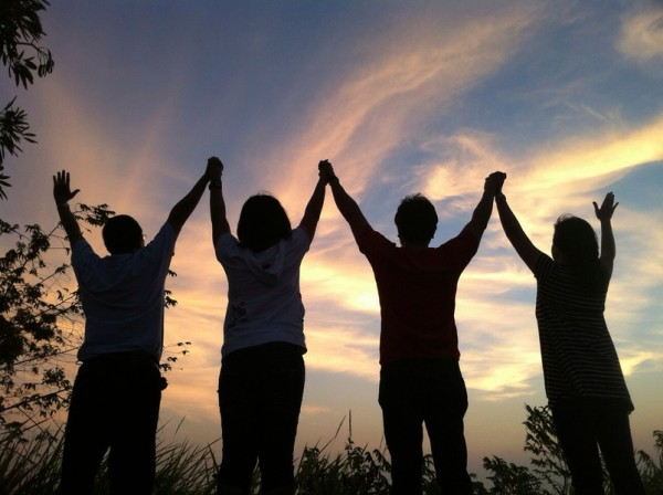 Silhouette friends raising hands together at dusk